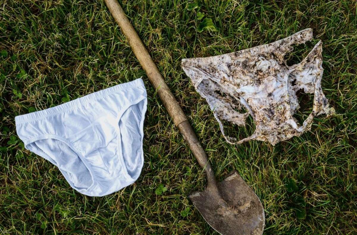 Eine Unterhose vor dem Vergraben und eine nach dem Ausgraben liegen neben einer Schaufel. In der Schweiz soll landesweit weiße Unterwäsche in der Erde verschwinden. Foto: Nicolas Zonvi/Agroscope/dpa