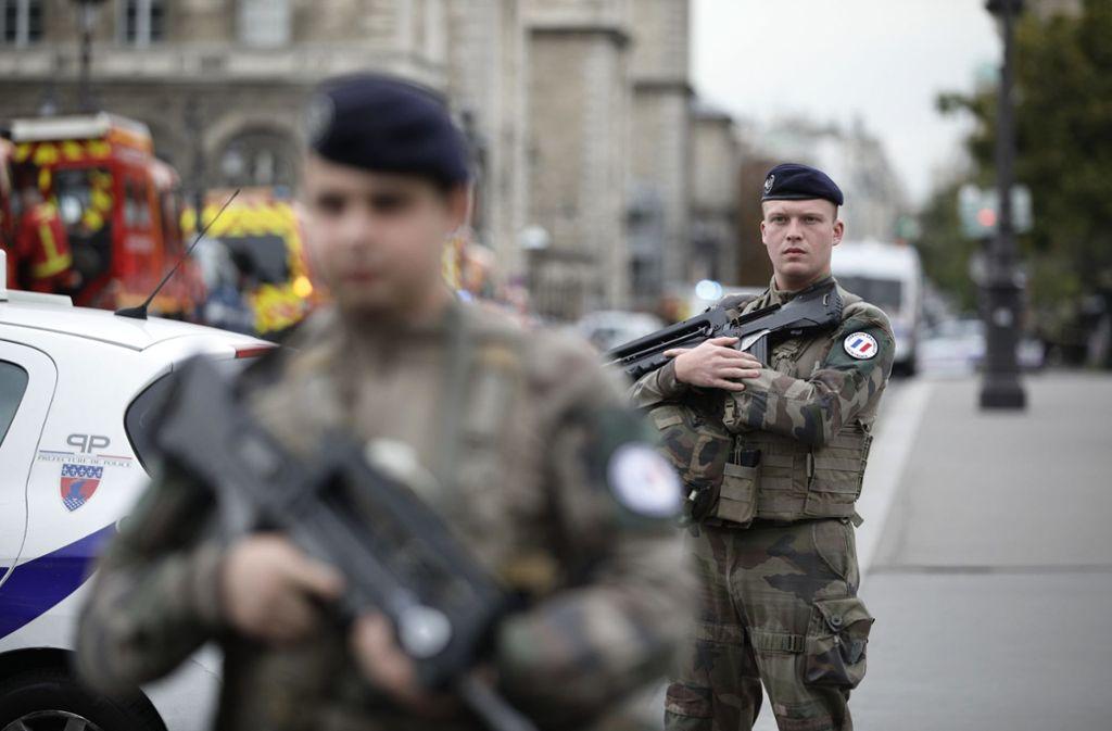 Bewaffnete Einsatzkräfte patrouillieren nach der Bluttat rund um die Pariser Polizeipräfektur Foto: dpa/Kamil Zihnioglu