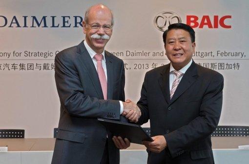Der Daimler-Vorstandsvorsitzende Dieter Zetsche und BAIC-Chef Xu Heyi geben sich die Hand, nachdem sie den Vertrag unterzeichnet haben. Foto: DAIMLERAG