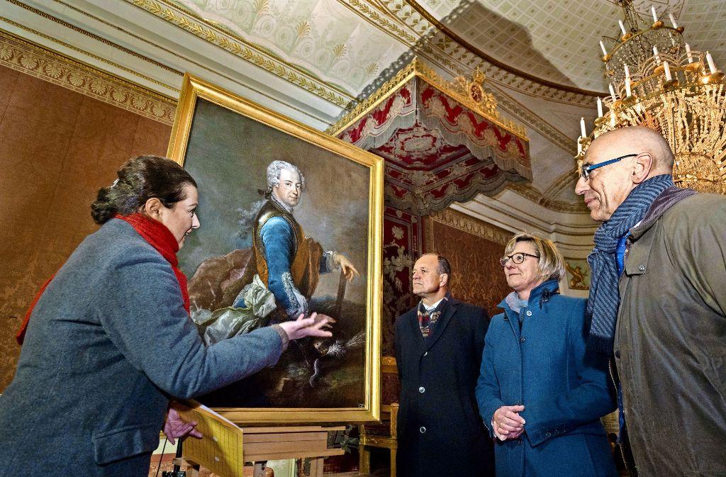 Die Restauratorin Patricia Peschel zeigt   Werner Spec, Finanzministerin Edith Sitzmann und Michael Hörrmann (von links)  das Werk. Foto: factum/Weise