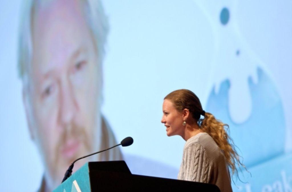 Die Wikileaks-Mitarbeiterin Sarah Harrison sprich in Hamburg im Congress Center (CCH) während des 30. Chaos Communication Congress (30C3) des Chaos Computer Clubs (CCC) mit Wikileaks-Mitbegründer Julian Assange, der auf einer Videoleinwand zu sehen ist. Foto: dpa