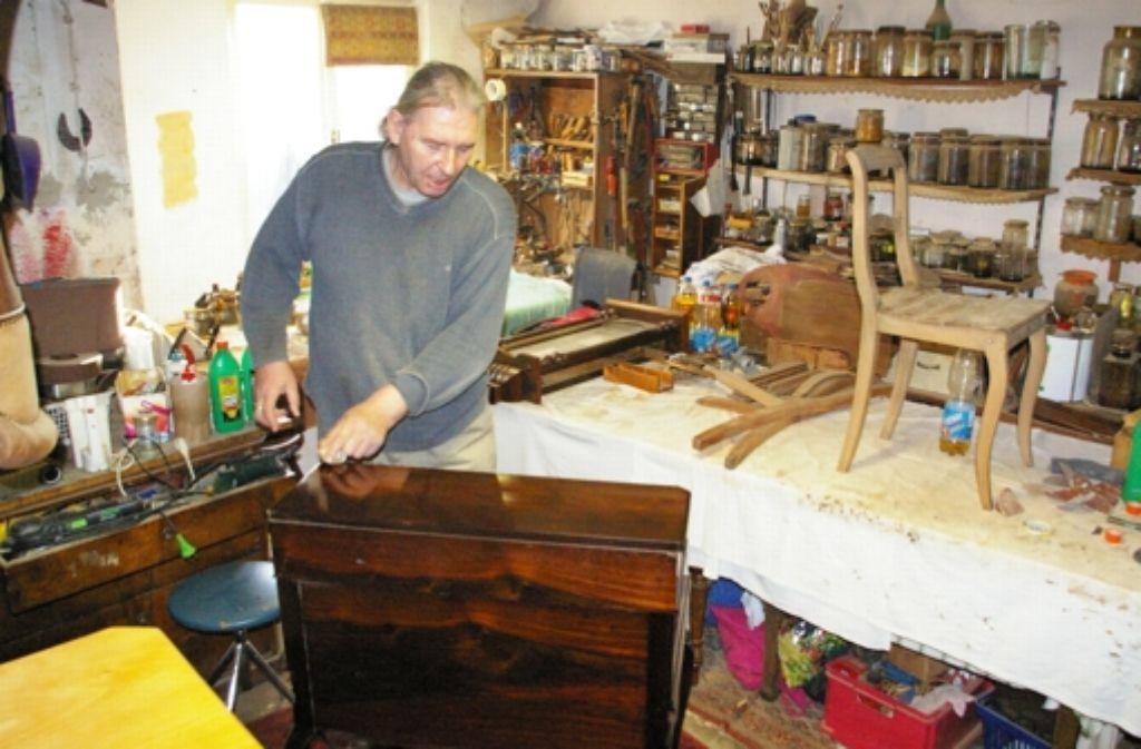 Ingo Hochmann bringt in der Garage an der Siedlerstraße 7 mit dem Naturprodukt Schellack einen alten Sekretär wieder auf Hochglanz. Foto: Alexandra Kratz