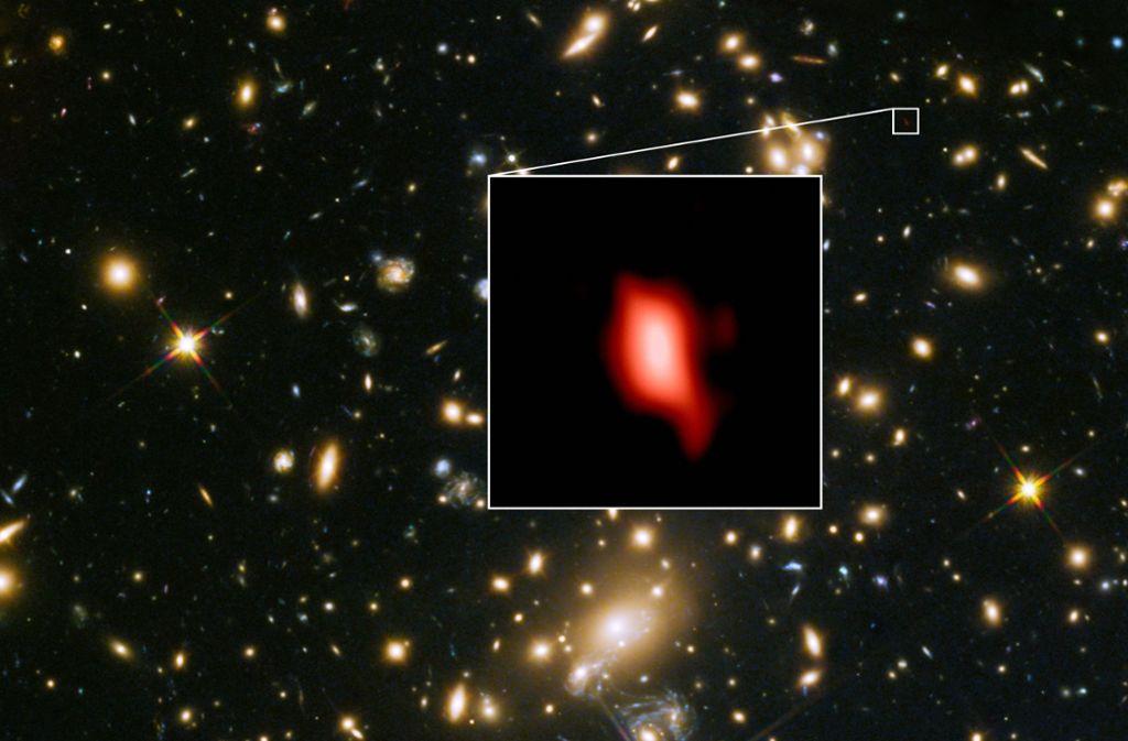 Das vom Hubble-Weltraumteleskop aufgenommene Bild zeigt die Galaxie MACS1149-JD1, die 13,28 Milliarden Lichtjahre von der Erde entfernt ist. Foto: ALMA (ESO/NAOJ/NRAO), NASA/ESA Hubble Space Telescope, W. Zheng (JHU), M. Postman (STScI), the CLASH Team, Hashimoto et al.