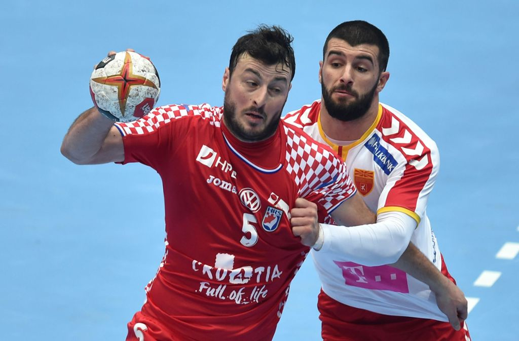 Domagoj Duvnjak (links) im Duell mit Martin Popovski. Foto: AFP/Christof Stache