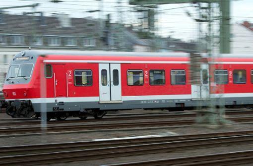 Mann stellt sich für Ehefrau vor abfahrbereite S-Bahn