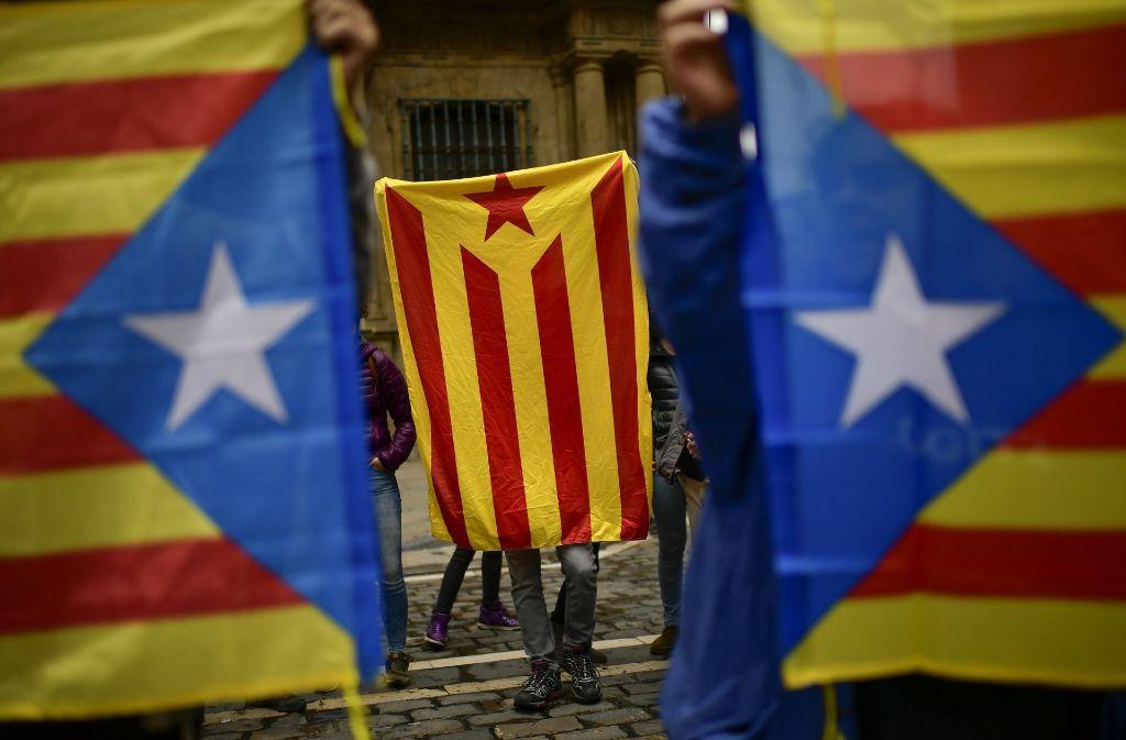 Menschen in Spanien halten am 1. Oktober die Flagge Kataloniens hoch. Foto: AP