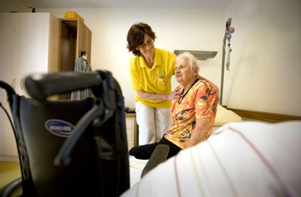 Sie verstehen  sich bestens: Die Ungarin  Zsuzsanna Dombovarine hilft  der Heimbewohnerin Meta Muck beim Aufstehen. Foto: Steinert