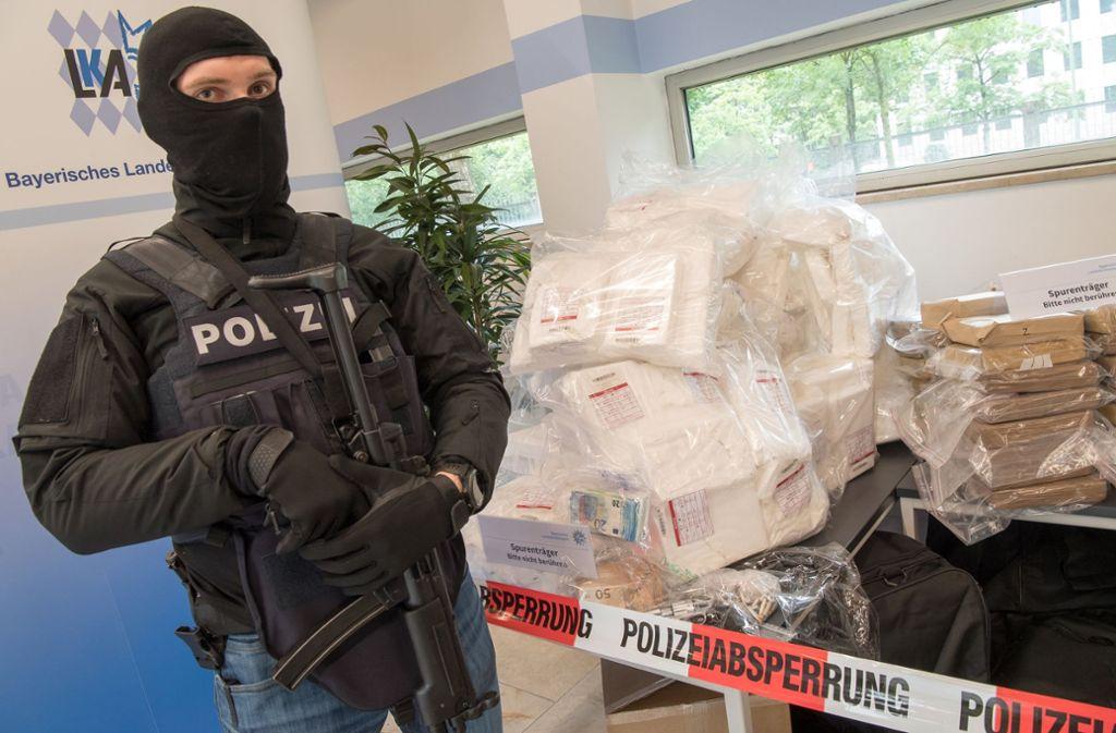 Schwer bewaffnete und vermummte Polizeibeamte bewachen während einer Pressekonferenz im bayerischen Landeskriminalamt etwa 640 Kilo Kokain, Waffen, Bargeld und Bananen aowie Bananenkisten Foto: dpa
