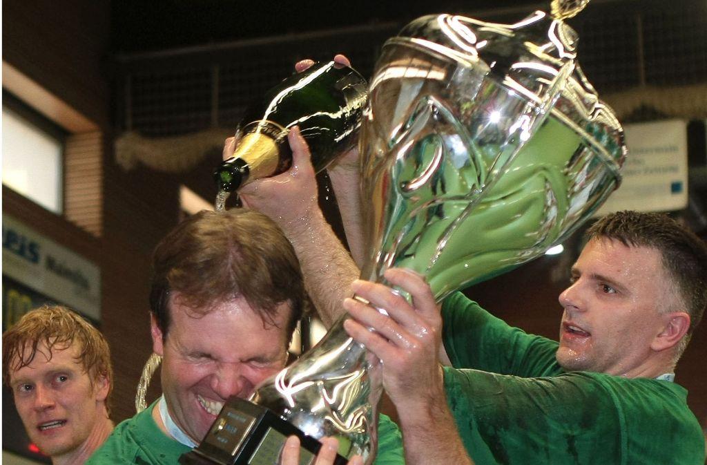 Göppinger Jubel: Geschäftsführer Gerd Hofele (Mi.) nach dem ersten EHF-Pokal-Triumph 2011 in Elsenfeld zusammen mit dem damaligen Torwart Enid Tahirovic (re.). Foto: Pressefoto Baumann