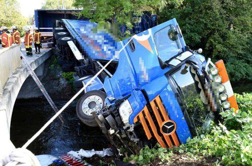 Fahrer bricht mit Lastwagen  durch Geländer und landet im Fluss