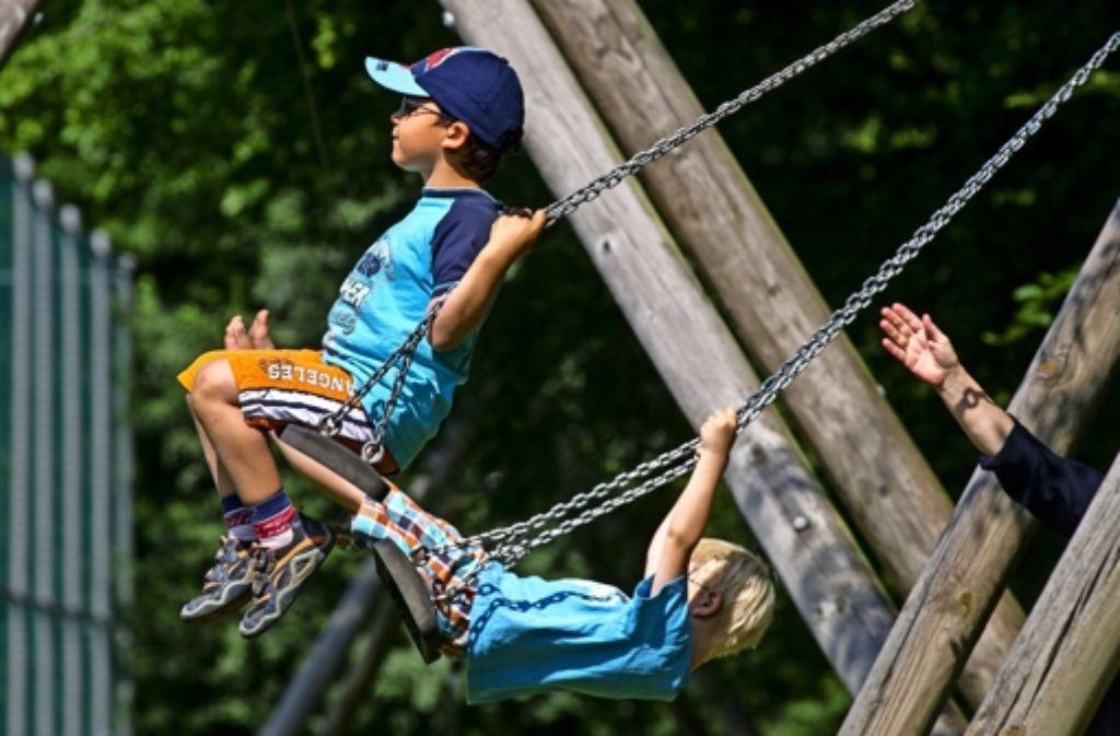 Zwei Jungen schaukeln auf dem Spielplatz des SOS-Kinderdorfs Foto: Frank Eppler