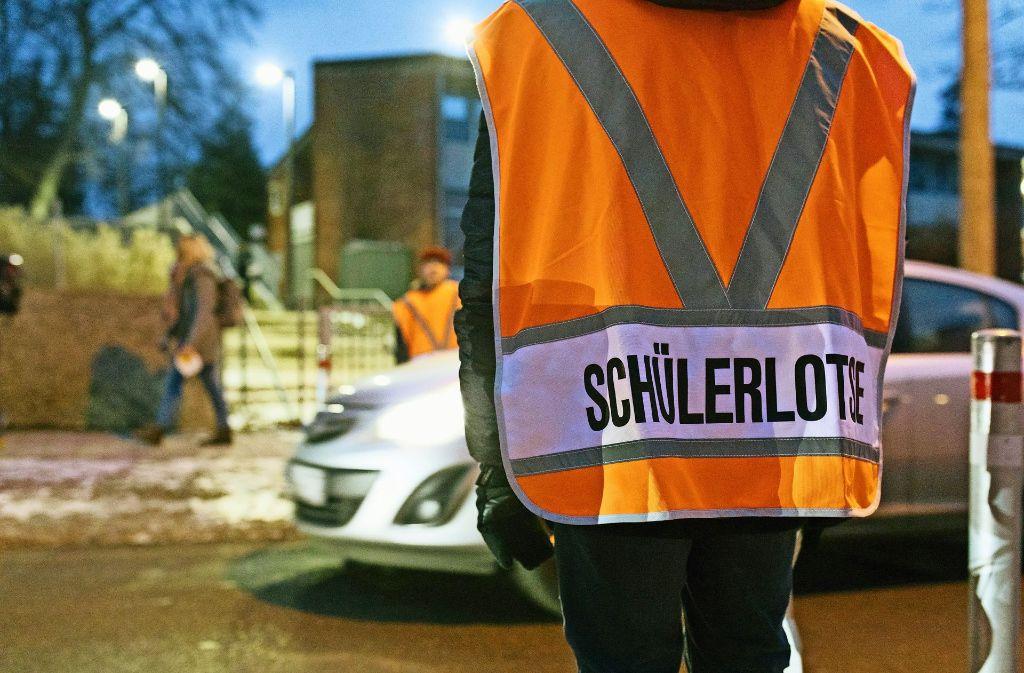 Ehrenamtliche sorgen dafür, dass die Kinder gefahrlos die Straße überqueren können, um  zur Altenburgschule zu gelangen. Doch  Verkehrsrowdys ist das egal. Foto: Lichtgut/Verena Ecker