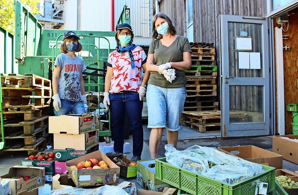 Marion Würth, Pia Hyvärinen und ihre Tochter Joana (v.r.), die auch manchmal mithilft, stehen vor Kisten mit geretteten Lebensmitteln Foto: Tilman Baur