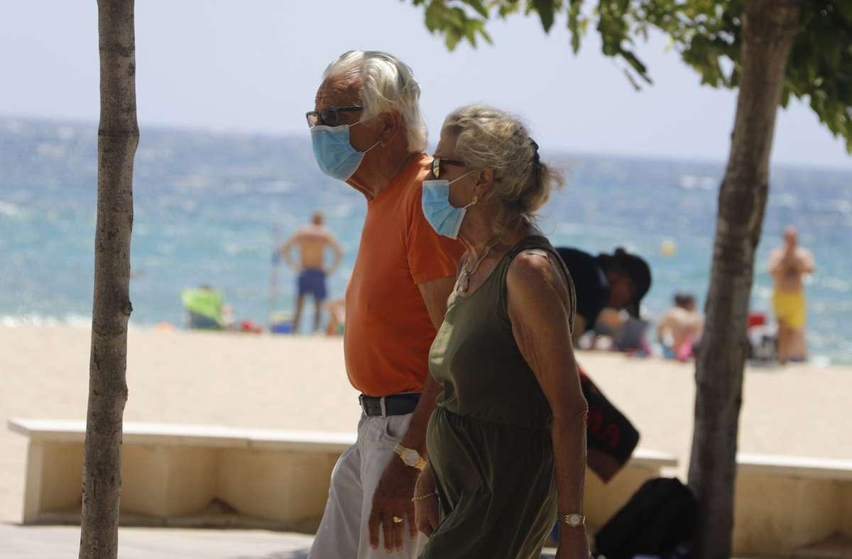 Maske am Strand  – trotzdem haben sich im Urlaub Tausende Reisende mit dem Coronavirus infiziert. Foto: dpa/Clara Margais