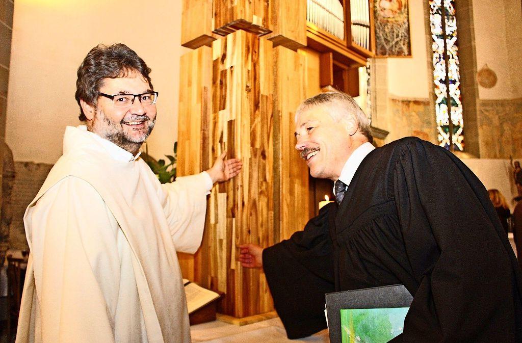 Pastoralreferent Jürgen Oettel (links) und Pastor Thomas Schmückle streicheln das Kreuz. Foto: Ute Jenschur