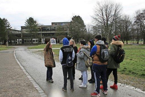 Elisabeth Marquart zeigt den sieben Schülern der Verbundschule Rohr  Schwarz-Weiß-Bilder aus der Vergangenheit Vaihingens an Ort und Stelle des Geschehens. Foto: Melissa Klug