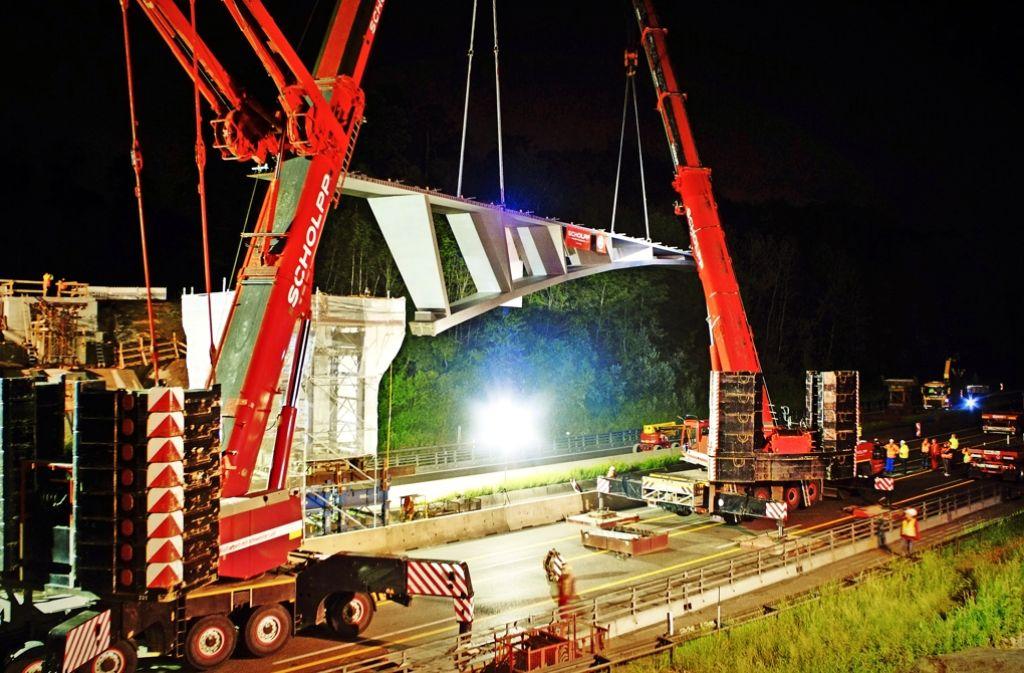 Präzisionsarbeit mit schwerem Gerät in der Nacht auf Sonntag: Das erste von zwei Teilen der neuen Bogenbrücke über die A8/81 wird montiert. Foto: RPS