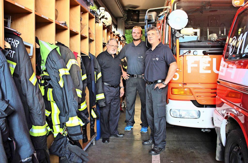Zwischen den geparkten Autos im Feuerwehrhaus sind gerade einmal drei Zentimeter Platz. Damit und mit vielen anderen Missständen wollen sich die Freiwilligen Feuerwehrleute Werner Rabe, Sebastian Zaiser und Thomas Burghard (v.l.) nicht mehr zufriedengeben. Foto: Caroline Holowiecki