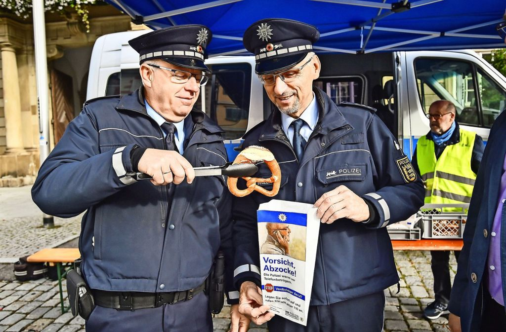 """Die Polizisten Alfred Seiter (links) und Paul  Mejzlik zeigen bei einer Aktion gegen Telefonbetrüger in diesem Monat in  Esslingen eine Brötchentüte mit der Aufschrift  """"Vorsicht Abzocke! Die Polizei warnt vor Telefonbetrügern"""". Foto: dpa/Ferdinando Iannone"""
