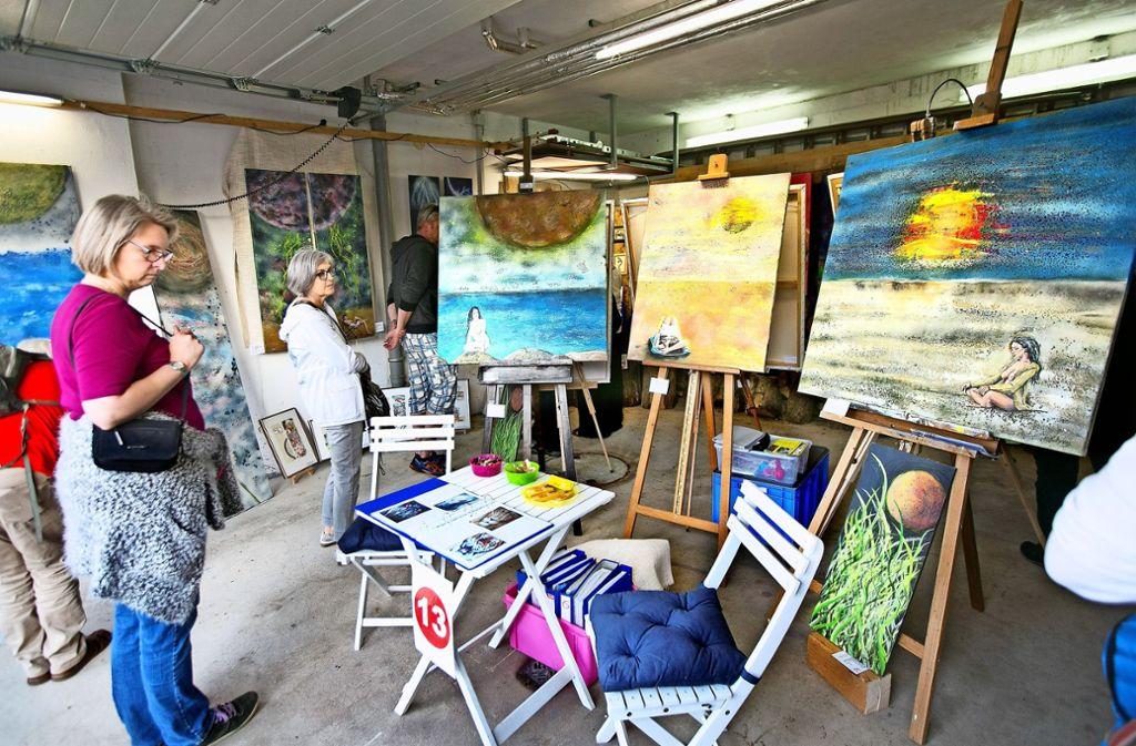 Passanten betrachten Bilder des Kunstmalers Claus Schrag in einer Garage. Foto: Horst Rudel