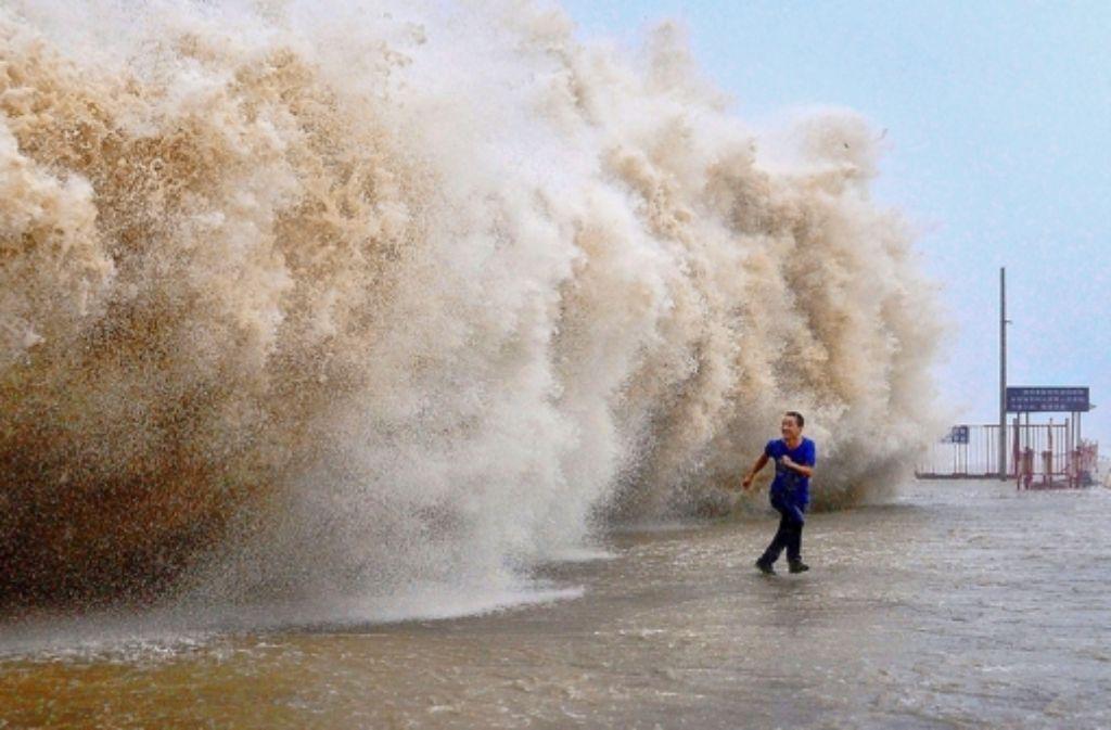 Bloß weg hier: ein Mann flüchtet vor einer Riesenwelle in Shantou. Foto:
