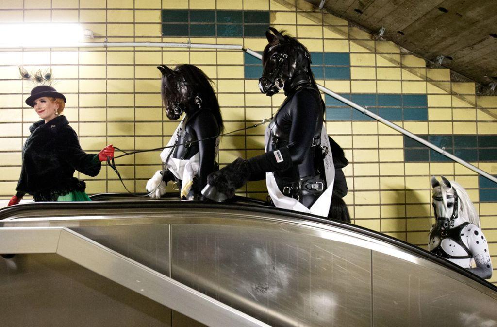 """Die Burlesque-Künstlerin Tronicat la Miez fährt am 16. Oktober 2015 in Hamburg mit einer Gruppe Fetisch-Liebhaber – sogenannte """"Petplayer"""" in Pferde-Outfits – im Rahmen einer Werbeaktion in einem U-Bahnhof eine Rolltreppe hoch. Foto: dpa"""