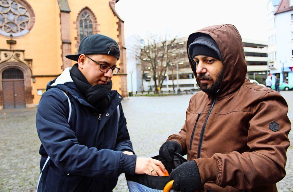 Fatih Ceylan steckt einem Obdachlosen vor der Leonhardskirche eine Orange in den Rucksack. Foto: Tilman Baur