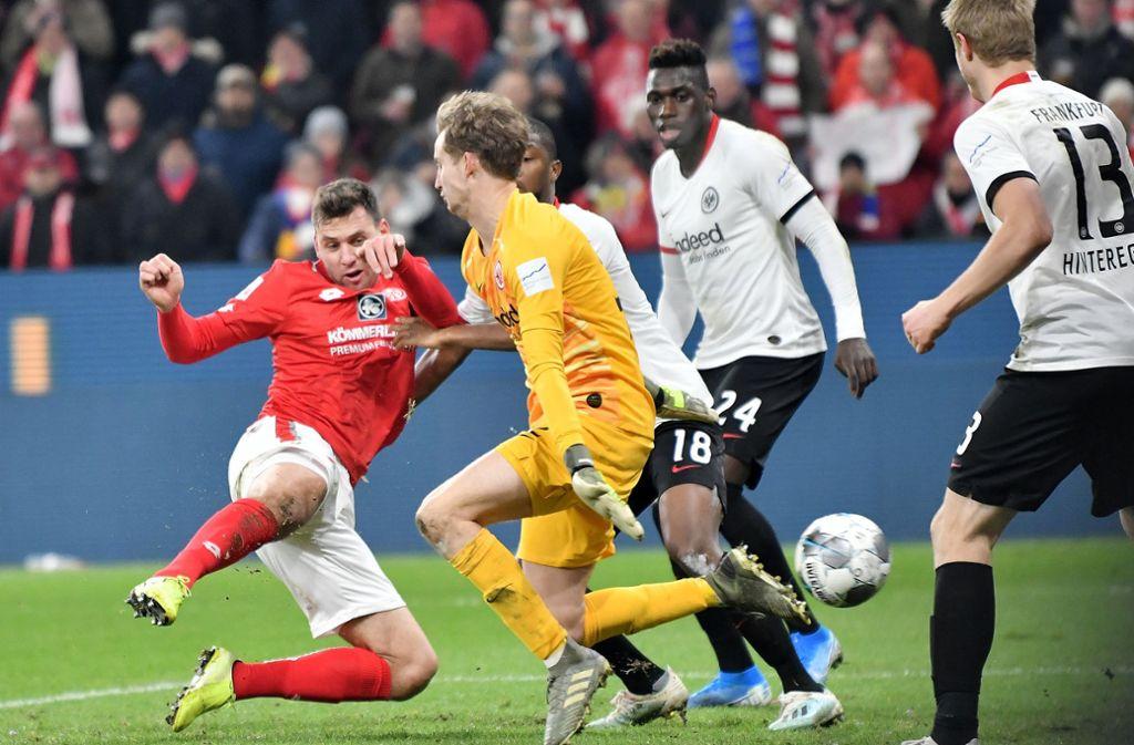 Der Mainzer Adam Szalai (l) trifft zum 2:1 gegen Frankfurts Torwart Frederik Rönnow. Foto: dpa/Torsten Silz