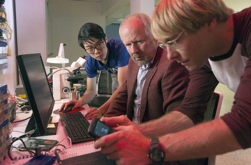 Die Cybercrime-Spezialisten Cao (Yung Ngo, links) und Dennis (Mirco Kreibich, rechts) überprüfen mit Klaus Borowski (Axel Milberg, Mitte) das Handy des Toten. Foto: NDR