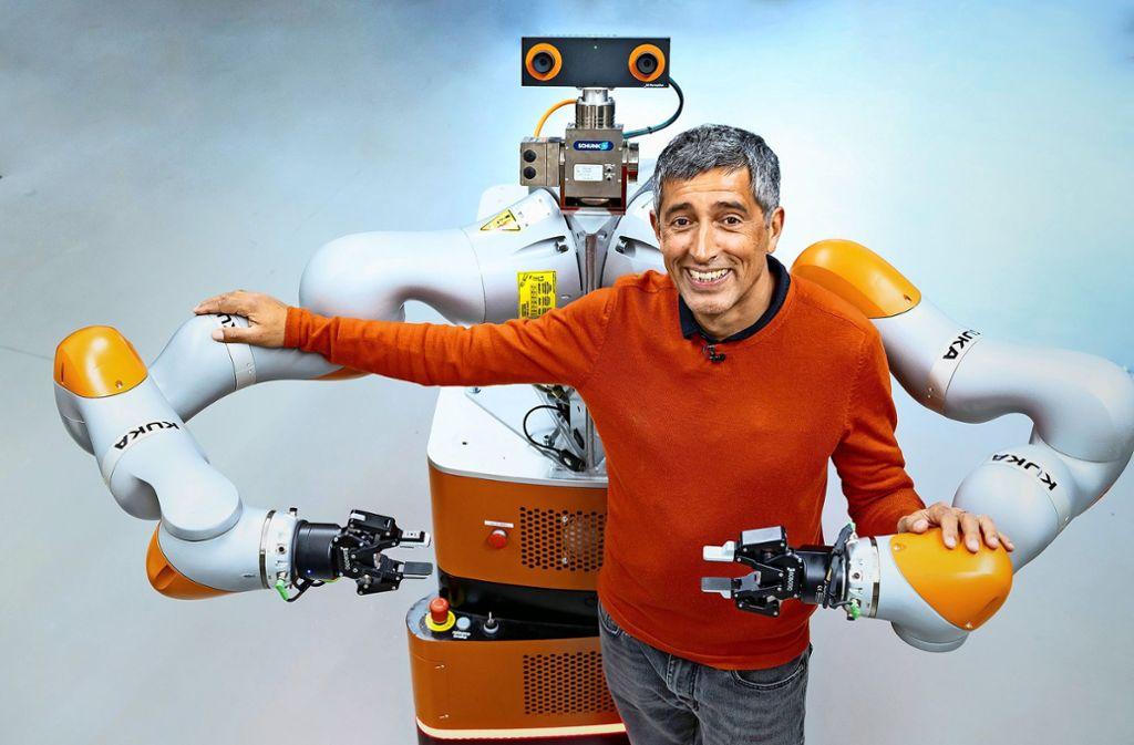 Ranga Yogeshwar untersucht, wie Künstliche Intelligenz unser Leben verändert. Hier lässt er sich von einem Roboter des Herstellers Kuka  in Augsburg umarmen. Foto: WDR