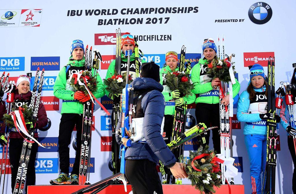 Deutliches Zeichen: Martin Fourcade verlässt während der Siegerehrung der Mixed-Staffeln das Podium, die siegreichen deutschen Biathleten schauen etwas verwundert. Foto: AFP