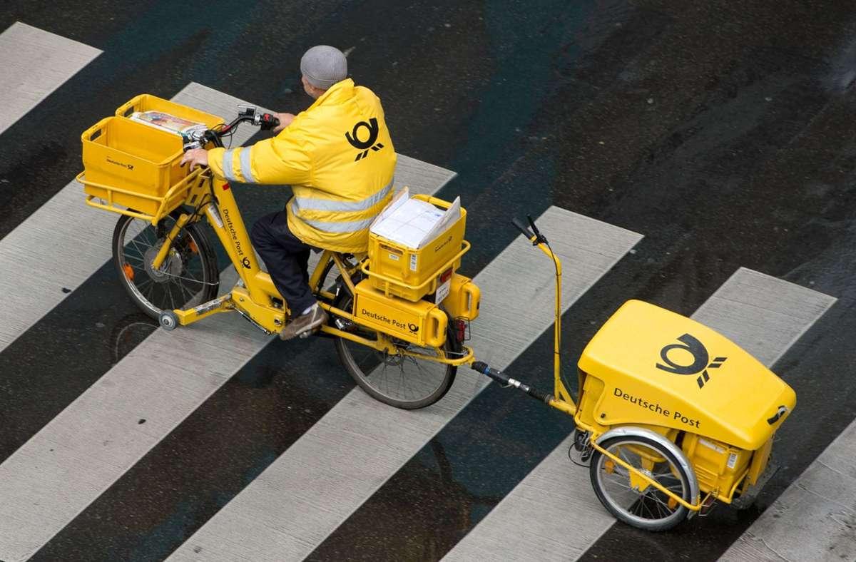 Ein Briefträger der Deutschen Post ist mit einem Fahrrad auf seiner Route unterwegs. Foto: dpa/Sebastian Kahnert