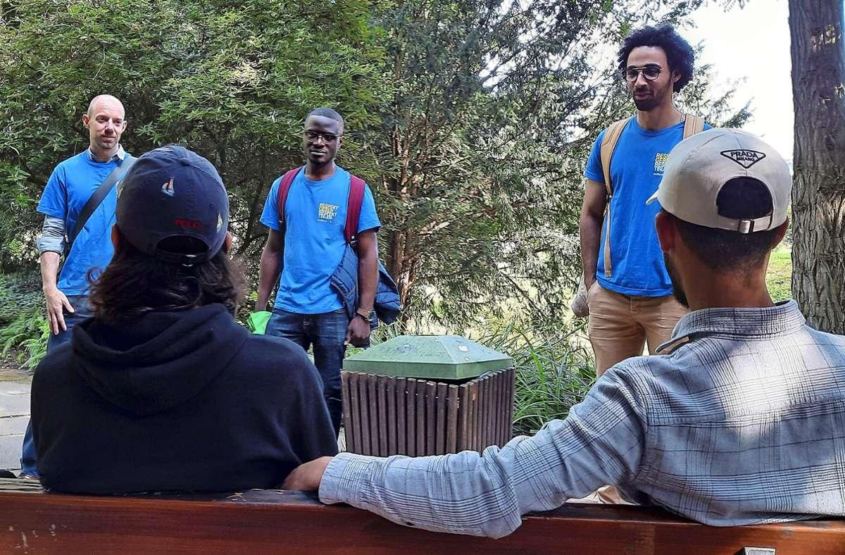 Kevin Gurka, Franky Koungang  und   Abdelrahman Mekki (v.l.) reden  mit jungen Männern aus Algerien. Foto: Eva Funke