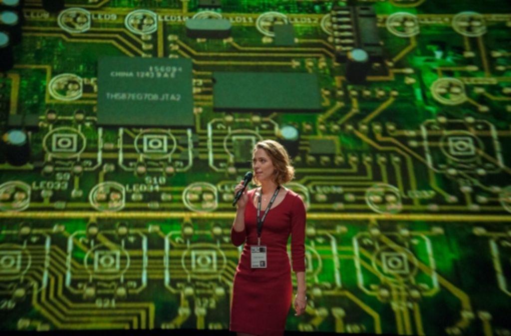 """Kleine Frau vor großen Chip: Rebecca Hall spielt in """"Transcendence""""  die Frau eines Professors für Künstliche Intelligenz und moderiert hier auf der Bühne einen Vortrag ihres Mannes an. Foto: Alcon Entertainment"""