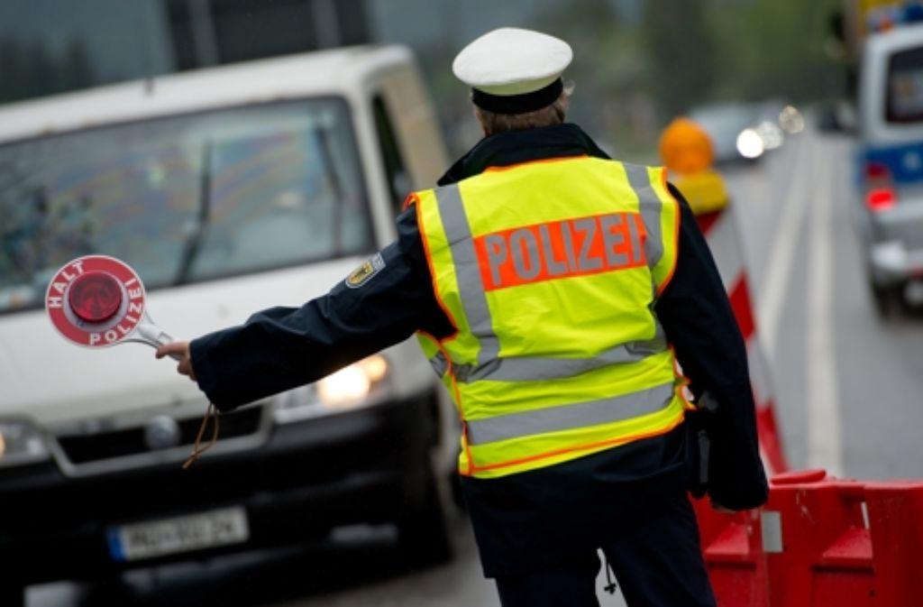 Ein Polizist kontrolliert nach Deutschland einreisende Autos. Foto: dpa