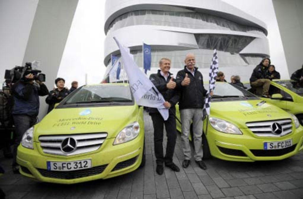 Daumen hoch: Thomas Weber, Forschungschef bei Daimler (Mitte links), und der Vorstandsvorsitzende Dieter Zetsche (mit Zielflagge) nehmen die Testfahrer und ihre neongrünen B-Klasse F-Cell nach 125 Tagen wieder in Empfang. Foto: dapd