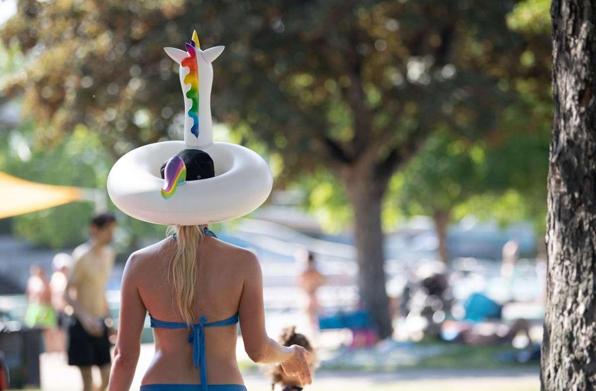 Im Inselbad in Untertürkheim hat sich eine Frau einen Einhorn-Schwimmreif auf den Kopf gesetzt. Foto: dpa/Sebastian Gollnow