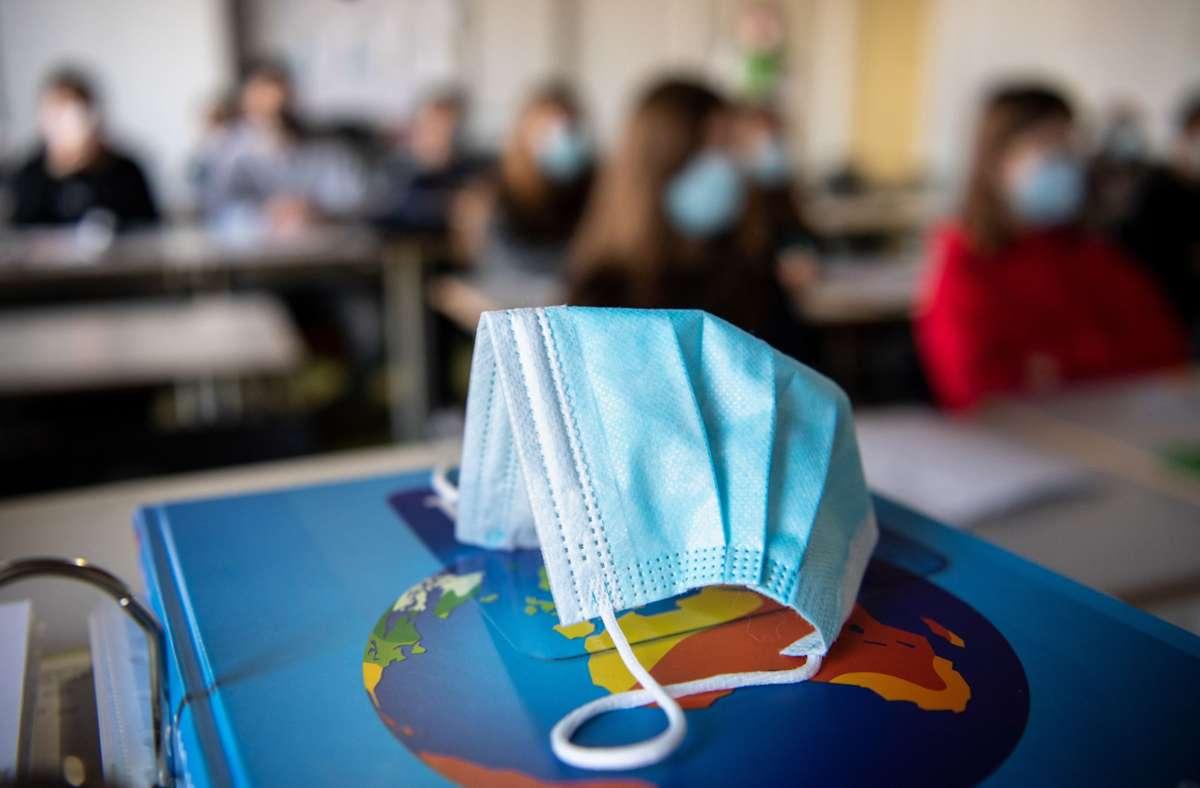 Ein Mund- und Nasenschutz liegt im Unterricht in einem Erdkunde-Unterricht, während im Hintergrund die Schülerinnen und Schüler mit Mund- und Nasenschutz zu sehen sind. Foto: Matthias Balk/dpa