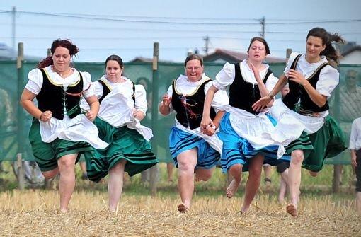 Gut zwanzig Jungen und Mädchen rennen beim traditionellen Schäferlauf in Markgröningen über ein Stoppelfeld. Foto: dpa