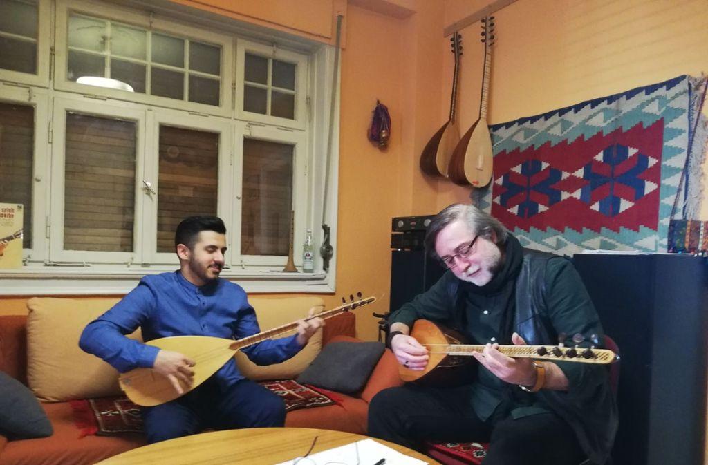 Der Lehrer Kadir Kaya und sein Schüler Hüseyin Demirci spielen auf der Langhalslaute Bağlama in der Musikschule Ezgi-Musikecke an der Dobelstraße. Foto: Cedric Rehman