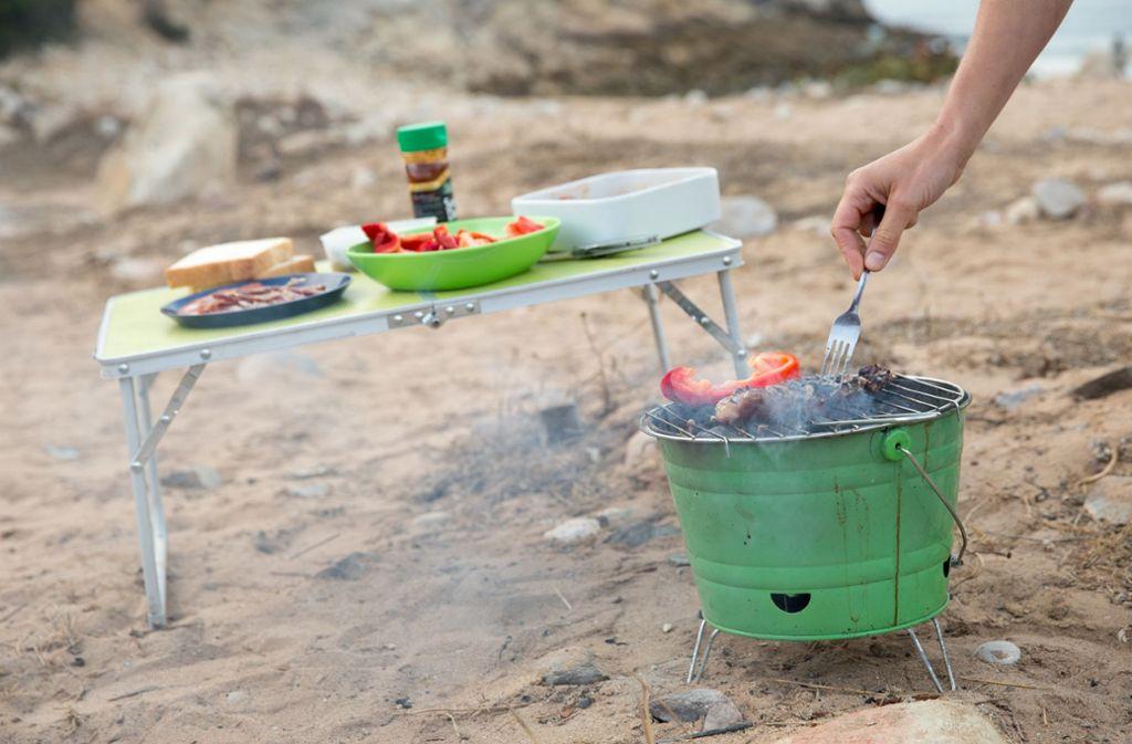 Wer campt, sollte mit Gasflaschen vorsichtig sei. Oder gleich am Grill das Essen brutzeln. Foto: dpa-tmn