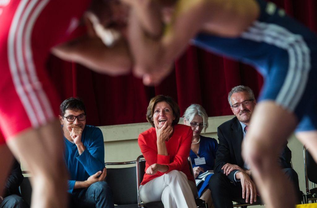 Die Mainzer Regierungschefin verfolgt vergnügt das Ringer-Training mit Flüchtlingen. Foto: dpa
