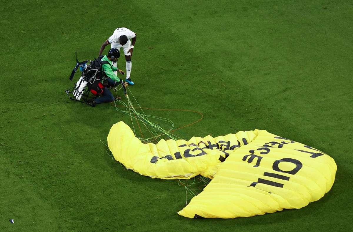 Nationalspieler Antonio Rüdiger erkundigt sich nach dem Befinden des Greenpeace-Aktivisten. Foto: dpa/Christian Charisius