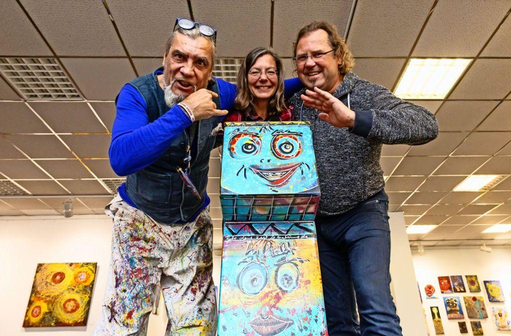 Der Künstler Andora, die Kunstbüro-Chefin Ina Penßler und der Werkstatt-Leiter Thomas Fietkau stehen vor dem Instrument, das 750 Euro einbrachte. Foto: Thomas Krämer