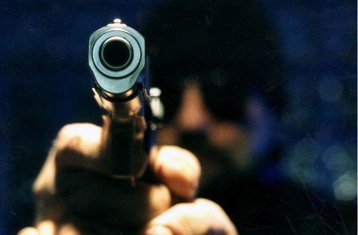 Junger Mann mit Pistole bedroht