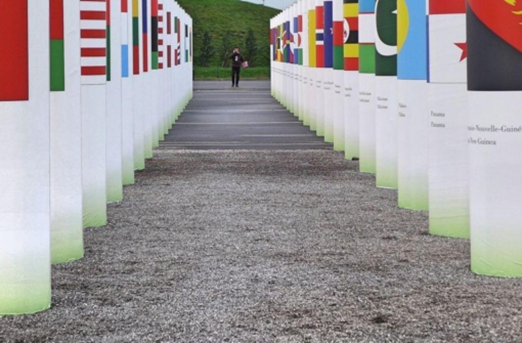 Vor dem Konferenzgelände des UN-Klimagipfels in Paris sind auf Säulen die Flaggen von 195 Staaten und der EU zu sehen. Man hat Mühe, in diesem bunten Wald sein eigenes Land zu finden, und bekommt einen Eindruck davon, wie viele Ansprüche und Wünsche in den Verhandlungen unter einen Hut gebracht werden müssen. – In einer Bildergalerie gibt es weitere Fotos von Protesten rund um den Klimagipfel. Foto: Mäder