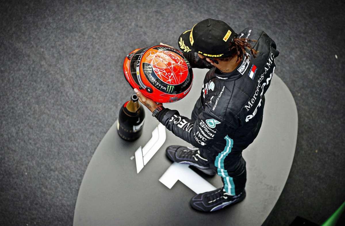 Lewis Hamilton hält den Helm von Michael Schumacher in den Händen und ist ergriffen von der Geste des Sohnes des Rekordweltmeisters. Foto: imago/Zak Mauger
