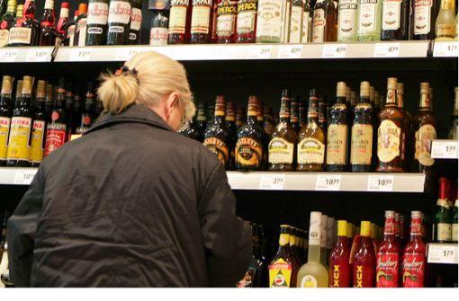 Frau entfernt Sicherungsetiketten von Spirituosen