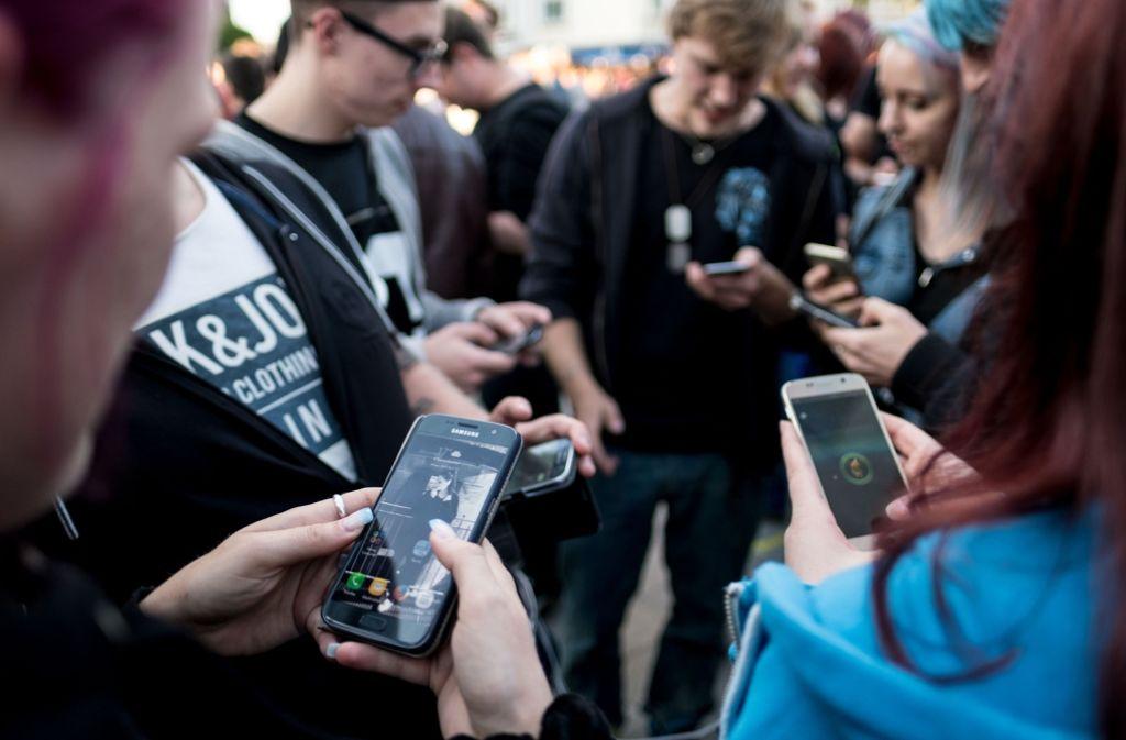 Junge Leute auf der Suche nach virtuellen Monstern Foto: dpa