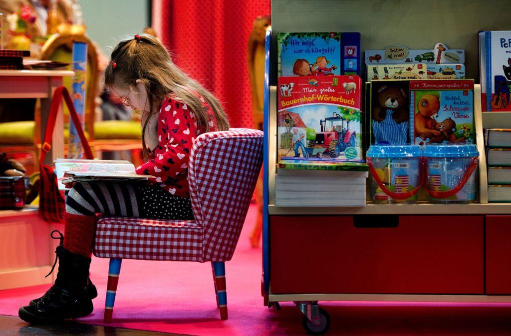 Versunken in eine andere Welt: Ein Mädchen ist auf der Leipziger Buchmesse in die Lektüre vertieft. Unsere Bildergalerie bietet 20 Anregungen für gute Kinder- und Jugendbücher. Foto: dpa